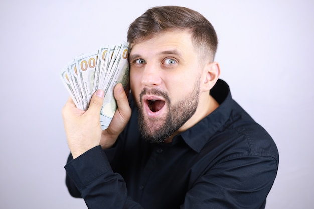 The man businessman pressed the money to his face and rejoices