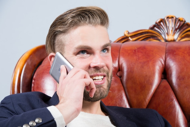 Man or businessman smile and talk on smartphone on sofa. business communication concept. entrepreneurship, new technology, modern life.