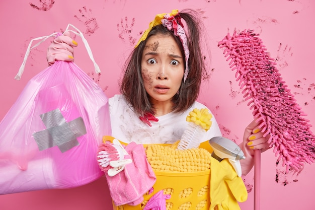 Man busy cleaning house collects rubbish in polythene bag holds mop poses near laundry basket isolated on pink