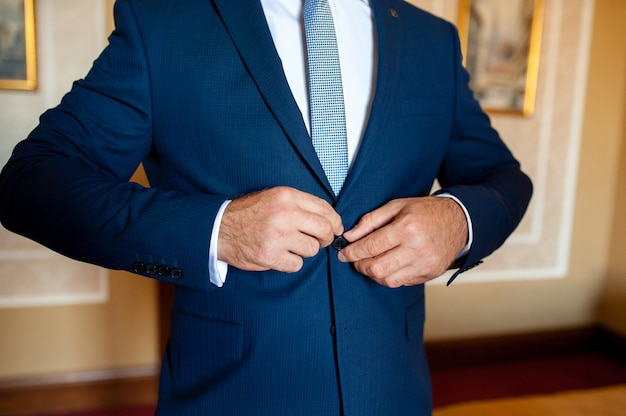 The man button blue suit.