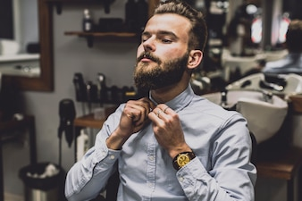 Man buttoning shirt in barbershop