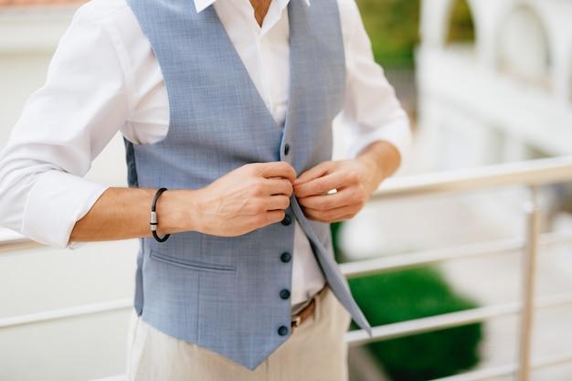 A man buttons his vest