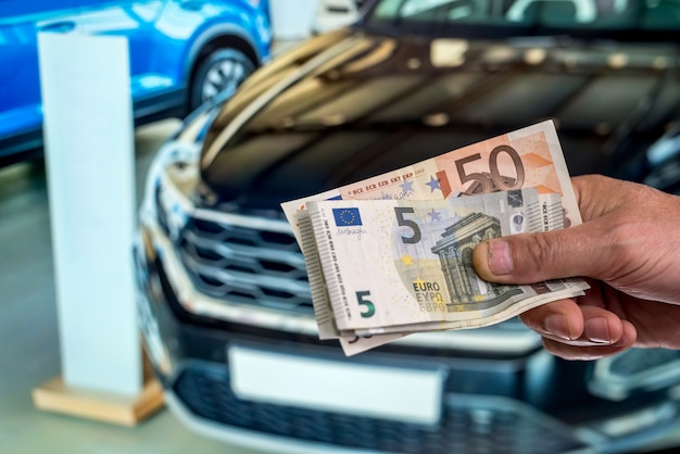 Man buy new car giving euro banknotes. finance purchase concept