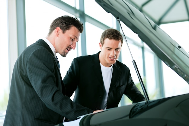 Man buying car from salesperson