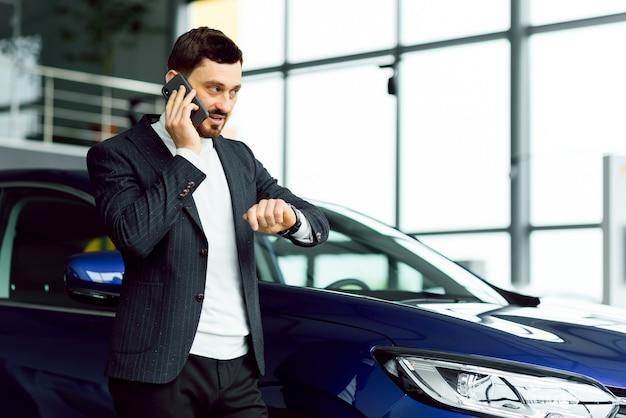 車を買う男。車のサロンのビジネスマン