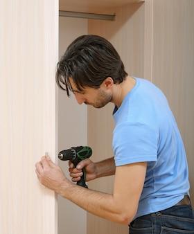 ネジをねじるドリルによる男。家具の組み立て