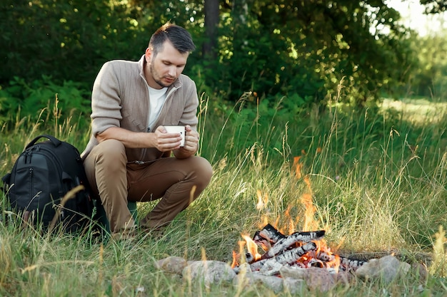 Man by the fire on green nature.