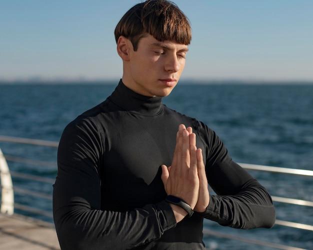 Человек на пляже медитирует