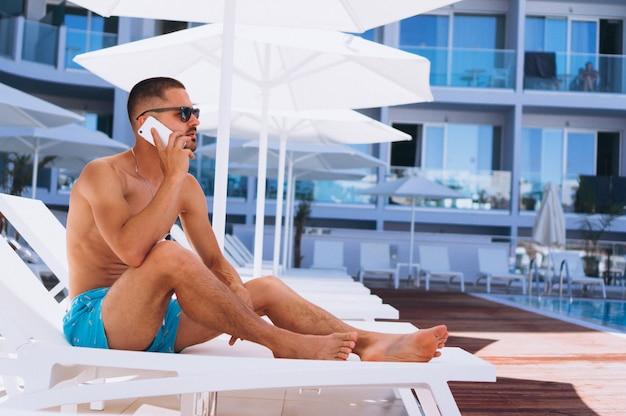 Человек у бассейна с телефоном