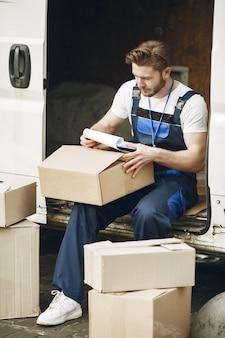 トラックの男。配達制服を着た男。クリップボードを持つ男。