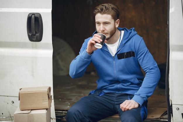 트럭으로 남자. 배달 유니폼을 입은 남자.