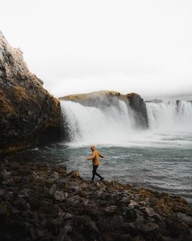 Человек у водопада идет по скалам