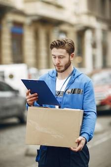 Uomo vicino al camion. ragazzo in uniforme da consegna. uomo con appunti.