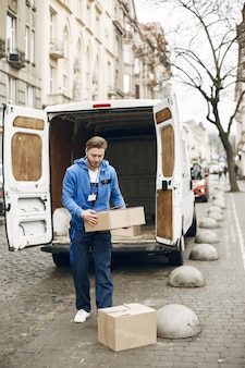 Man by the truck. guy in a delivery uniform.