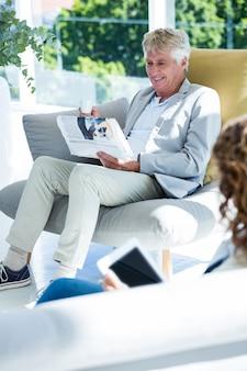 Мужчина за женщиной читает газету у себя дома