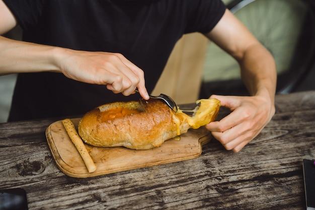 L'uomo nel caffè ha zuppa in un piatto di pane.