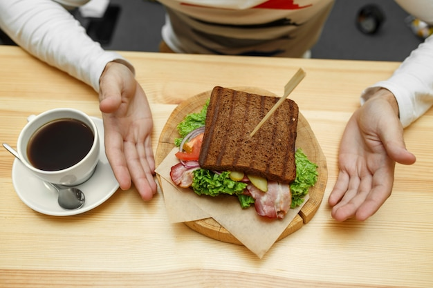 Man in cafe take his order sandwich and coffee