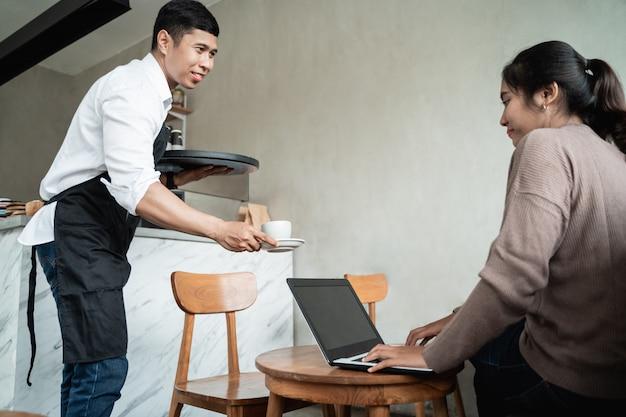 Человек официант кафе приносит заказы на чашку кофе