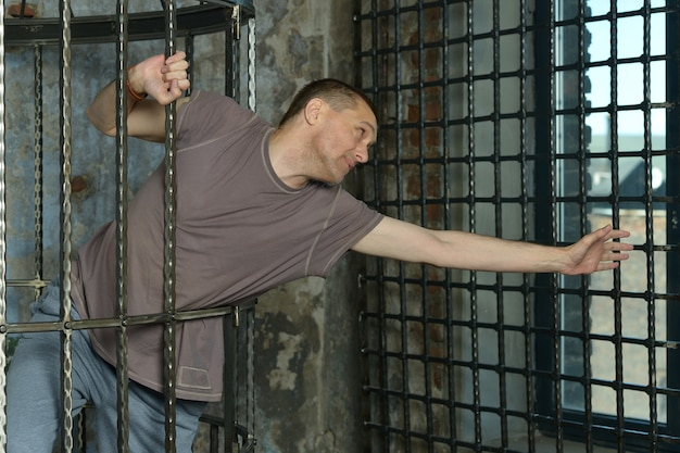 Man in cage with hands on steel lattice