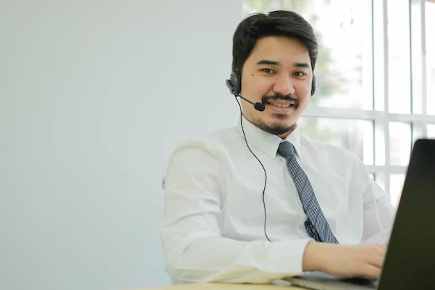 男性のコールセンターのエージェントはヘッドセットデバイスを着用し、サービスマインドと手術室で働いて笑顔