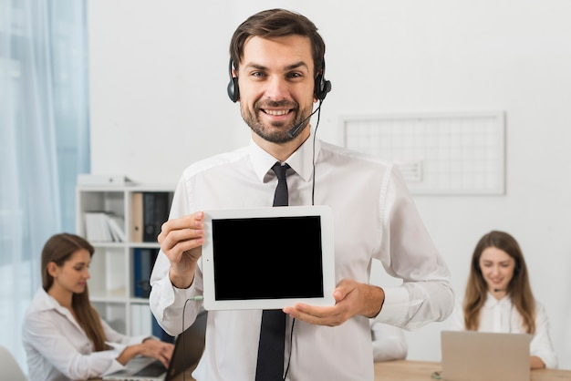 Man in call center showing tablet