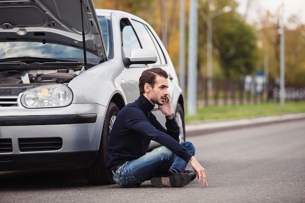 그의 손상된 자동차에 대한 도움을 얻기 위해 전화로 전화하는 남자