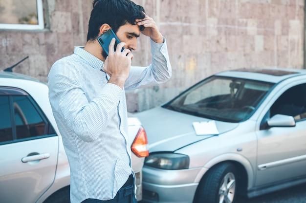 交通事故の後に応急処置を呼ぶ男