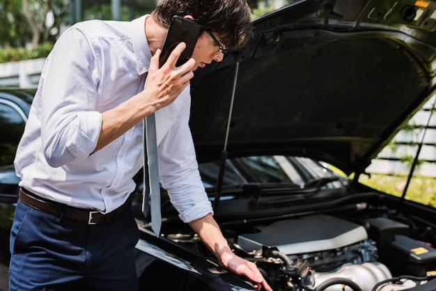 그의 차를 고치기 위해 도움을 청하는 남자