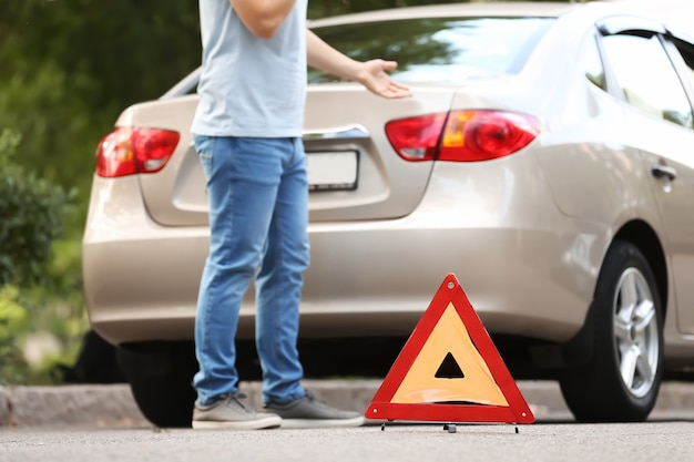 Man calling his insurance agent while standing near broken car on road