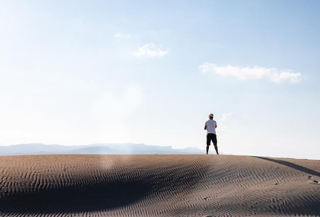 Человек звонит с подставкой для смартфона в пустынных дюнах в одиночку, копирует пространство