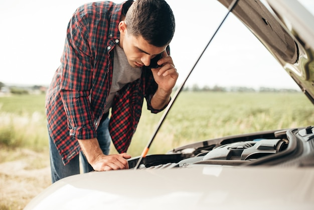 Man calls to emergency service,while looking on motor of broken car. trouble with vehicle on road in summer day