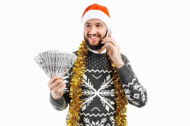 Man calls on the phone with money in his hands new year concept