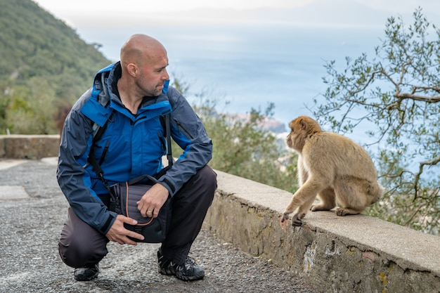 A man can see a monkey in a nature reserve in gibraltar