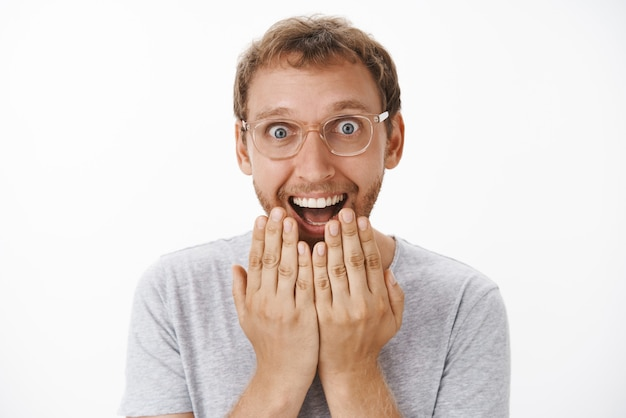 Man cannot hide happiness and excitement receiving awesome news holding palms above mouth smiling broadly with astonished pleased expression staring amazed