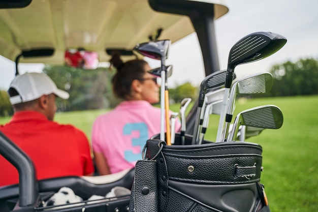 Man in a cap and a dark-haired woman riding in a golf car
