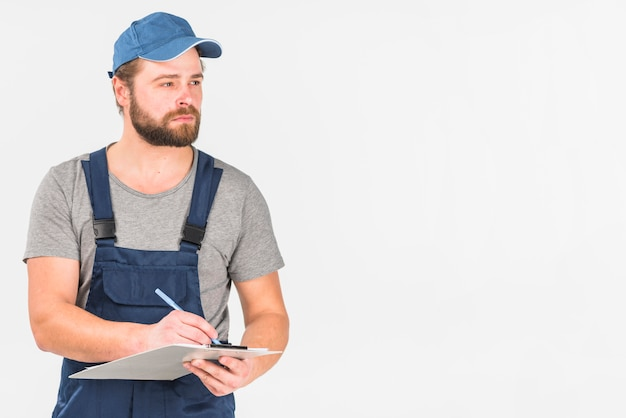 Man in cap and overall writing on clipboard