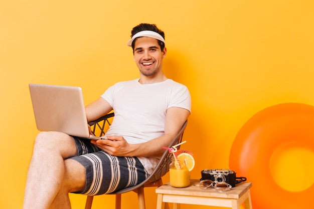 Man in cap, white t-shirt and striped shorts works in laptop, enjoying cocktail.