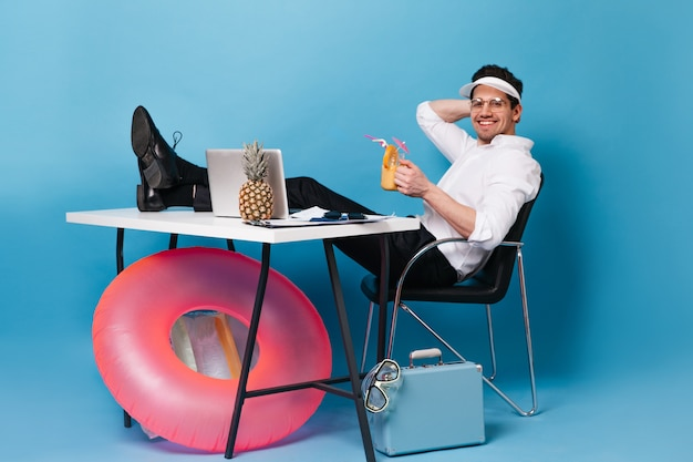 Man in cap works on vacation and drinks cocktail. guy is sitting at table with suitcase, inflatable circle, laptop and pineapple.