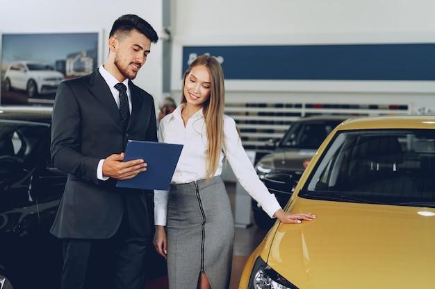 車のサロンで女性のバイヤーに新しい車を示す男性車ディーラー