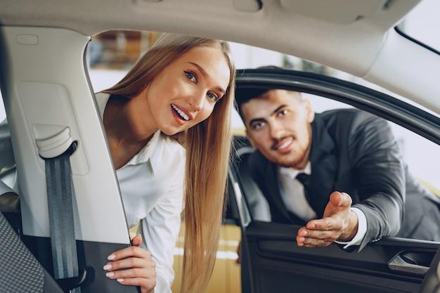 Дилер автомобилей мужчина показывает покупательнице новую машину в салоне автомобиля