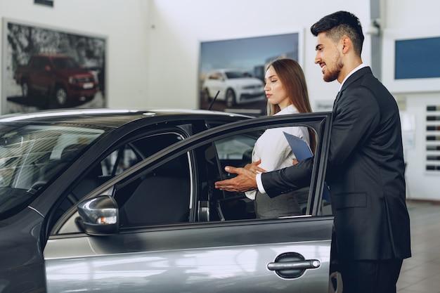 Мужчина-автодилер показывает покупательнице новую машину