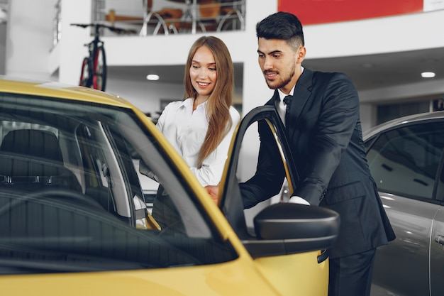 Man car dealer showing a woman buyer a new car in car salon