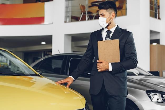 彼の職場、コロナウイルス防止の概念に防護マスクを身に着けている男の車のディーラー