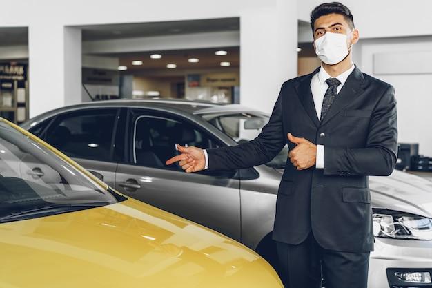 Мужчина автодилер в защитной медицинской маске на своем рабочем месте, концепция профилактики коронавируса