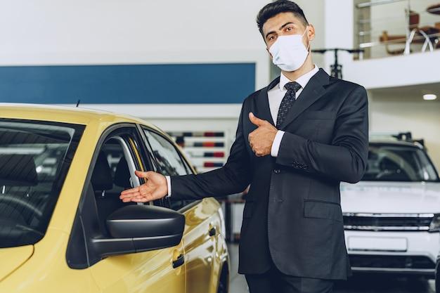 彼の職場で保護医療マスク、コロナウイルス予防コンセプトを身に着けている男の車のディーラー