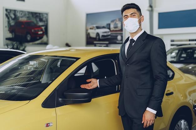 彼の職場で防護マスクを身に着けている男の車のディーラー