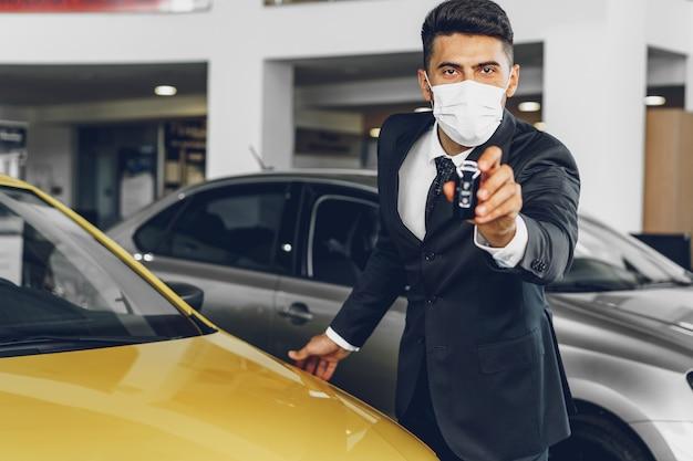 彼の職場で保護医療マスクを身に着けている男の車のディーラー