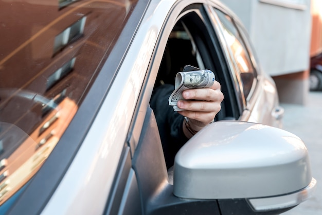 Man in car holding dollar for bribe or pay in goods. business finance concept