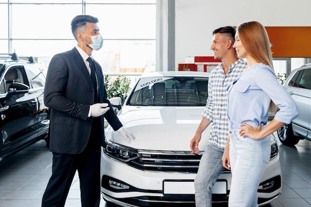 Продавец автомобилей человек в маске разговаривает с клиентом в автосалоне
