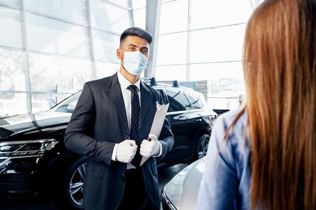 Продавец автомобилей человек в маске разговаривает с клиентом в выставочном зале